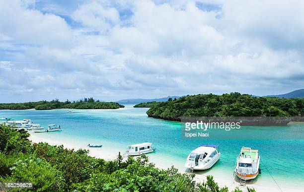 Tropical lagoon beach, clear blue water and boats