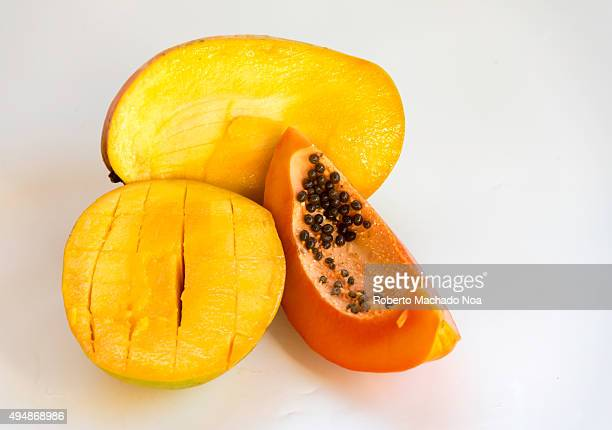 Tropical mango fruit cut into two pieces along with a slice of ripe papaya on white background
