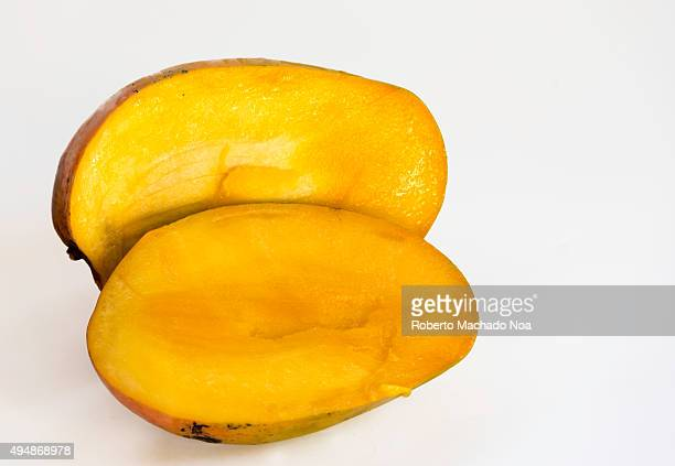 Tropical mango fruit cut into two pieces on white background