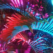 This is a square color photograph of tropical palm tree fronds illuminated with multi-colored lights at night in Wynwood Miami Florida.