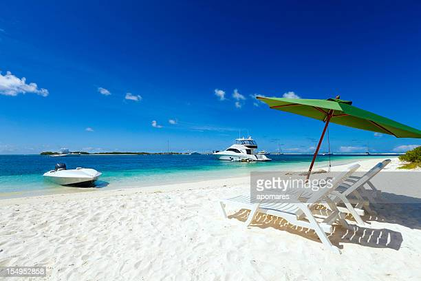 Tropical paradise with lounge chairs umbrella and a yacht