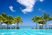 Tropical beach resort with  lounge chairs and umbrellas in Mauritius