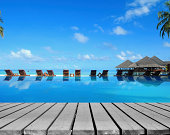 Tropical resorts swimming pool with empty wooden platform -- Summer holidays concept