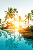Outdoor pool area at a tropical resort during sunset.