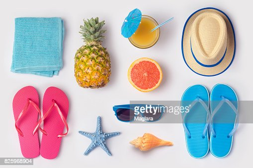 Tropical summer vacation concept with pineapple, juice and flip flops organized on white background. View from above. Flat lay : Stock Photo