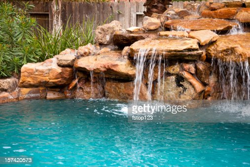 Tropical swimming pool with rock waterfall stock photo for Pool design company elwira kowalska