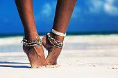 Beautiful female legs on a white sandy beach. dressed in traditional Maasai jewelry. Zanzibar. Tanzania