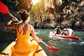 Beautiful lady and friends walks by kayaks at sea bay between big rocks
