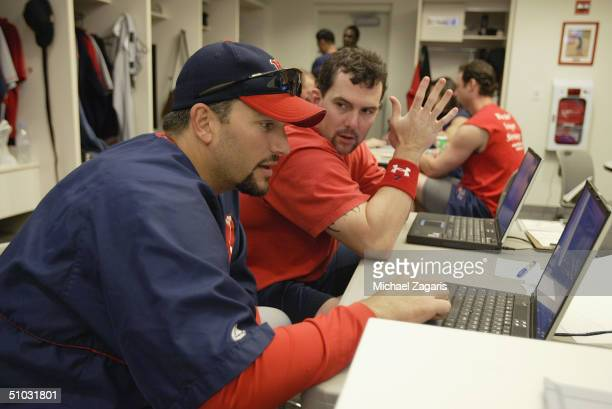 Trot Nixon and Doug Mirabelli of the Boston Red Sox study their at bats on a computer in the locker room before the MLB game against the San...