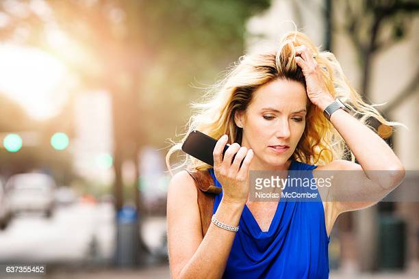 Troubled mature woman listening to bad news on speaker phone