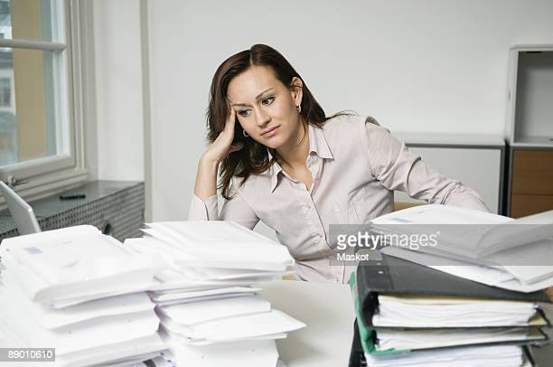 Troubled woman behind piles of envelopes