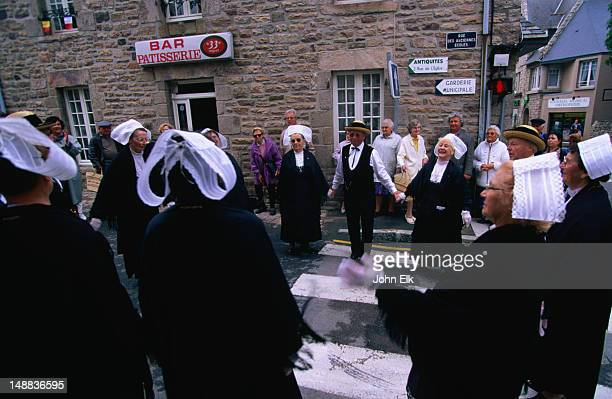 A troupe of traditional Breton dancers in their black costumes with white headdresses, performing in the street