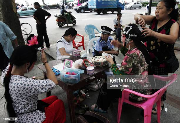 Troupers remove stage makeup and costumes after performing Chu Opera on a street stage during an intangible cultural heritage show held to mark the...
