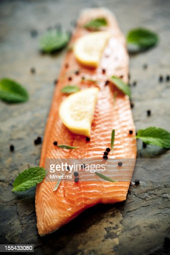 Trout fillet with lemon and capers on a stone surface