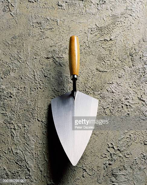 Trowel placed on rough cement, close-up