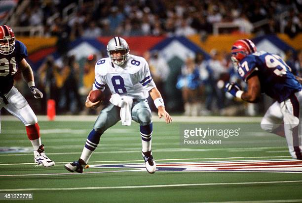 Troy Aikman of the Dallas Cowboys scrambles with the ball pursued by Cornelius Bennett of the Buffalo Bills during Super Bowl XXVIII on January 30...