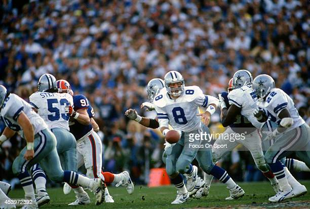 Troy Aikman of the Dallas Cowboys turns to hand the ball off to running back Emmitt Smith against the Buffalo Bills during Super Bowl XXVII on...
