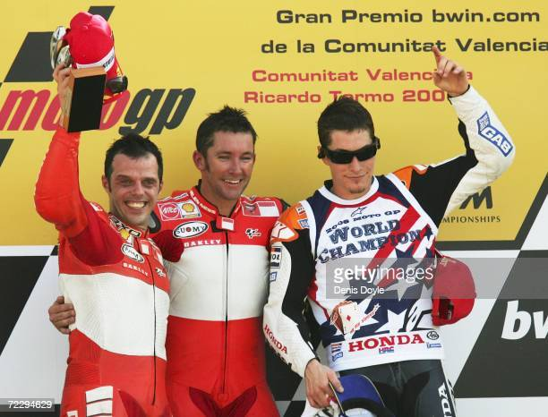 Troy Bayliss of Australia celebrates on the podium with Loris Capirossi of Italy and Nicky Hayden of the US after they finished first second and...