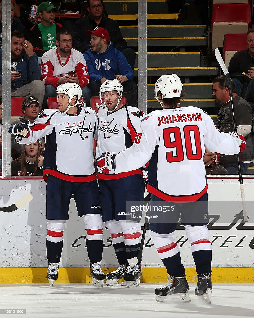 Troy Brouwer #20 and Marcus Johansson #90 of the Washington Capitals celebrate with teammate Brooks Laich #21 after a goal during an NHL game against the Detroit Red Wings at Joe Louis Arena on November 15, 2013 in Detroit, Michigan.