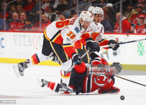 Troy Brouwer of the Calgary Flames checks Adam Henrique of the New Jersey Devils during the third period at the Prudential Center on February 3 2017...