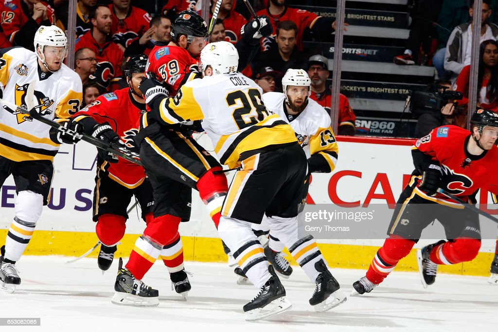 Troy Brouwer #36 of the Calgary Flames is checked by Ian Cole #28 of the Pittsburgh Penguins during an NHL game on March 13, 2017 at the Scotiabank Saddledome in Calgary, Alberta, Canada.