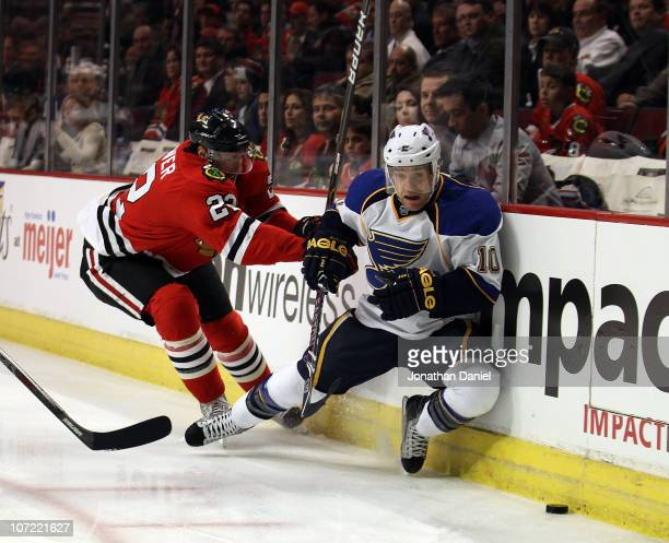 Troy Brouwer of the Chicago Blackhawks knocks down Andy McDonald of the St Louis Blues as they battle for the puck at the United Center on November...