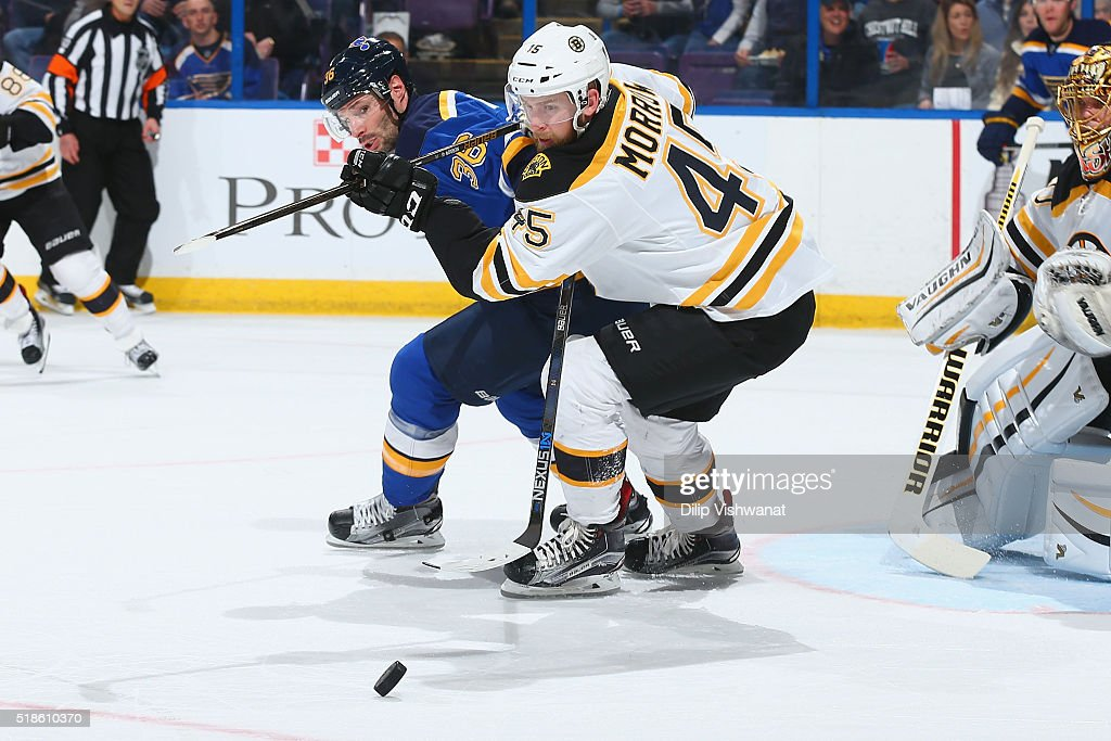 Troy Brouwer of the St Louis Blues and Joe Morrow of the Boston Bruins chase down the puck at the Scottrade Center on April 1 2016 in St Louis...