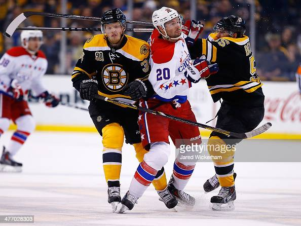 Troy Brouwer of the Washington Capitals is hit by Carl Soderberg and Johnny Boychuk of the Boston Bruins in the second period during the game at TD...