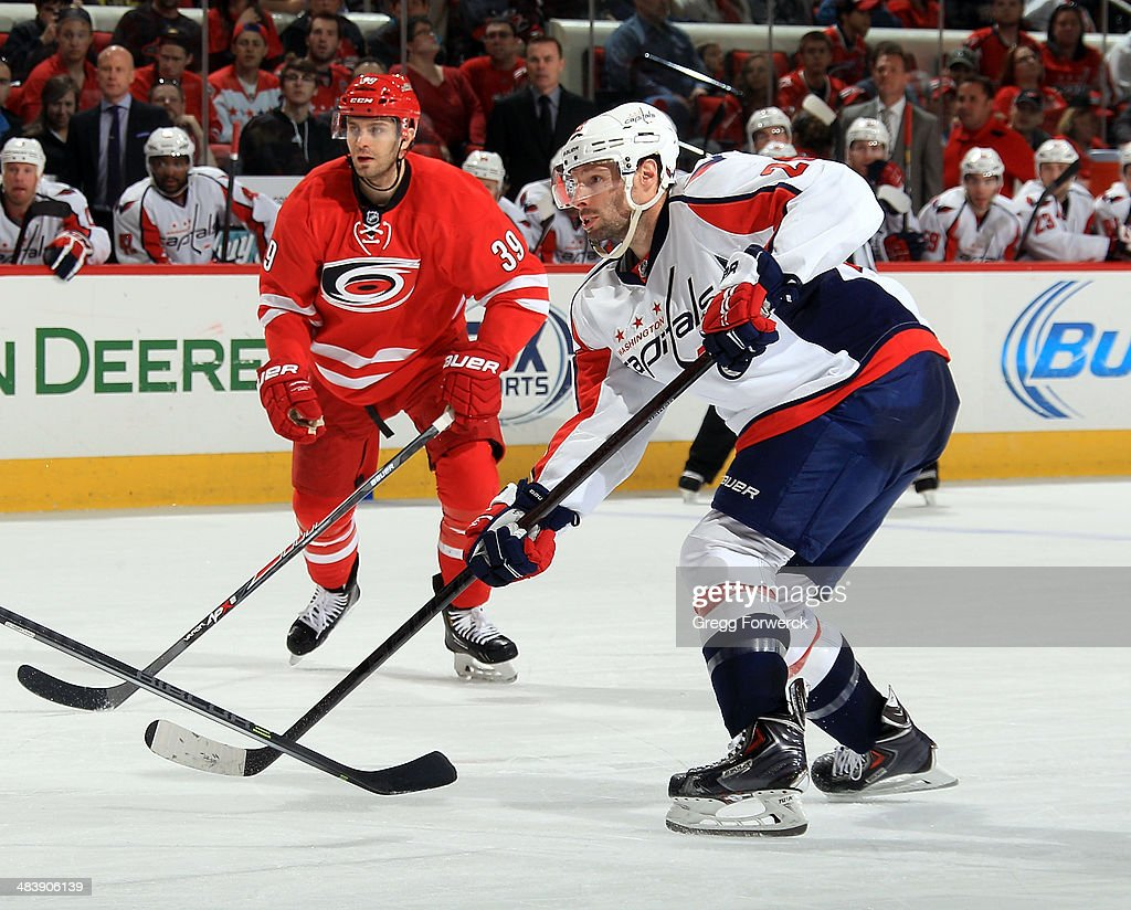 <a gi-track='captionPersonalityLinkClicked' href=/galleries/search?phrase=Troy+Brouwer&family=editorial&specificpeople=4155305 ng-click='$event.stopPropagation()'>Troy Brouwer</a> #20 of the Washington Capitals shoots the puck as Patrick Dwyer #39 of the Carolina Hurricanes looks on during their NHL game at PNC Arena on April 10, 2014 in Raleigh, North Carolina.