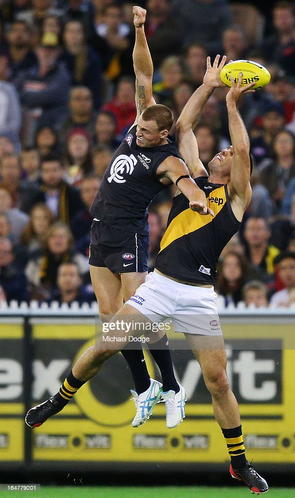 A Troy Chaplin of the Tigers marks the ball against Mitch Robinson of the Blues during the round one AFL match between the Carlton Blues and the Richmond Tigers at Melbourne Cricket Ground on March 28, 2013 in Melbourne, Australia.