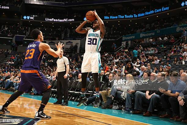 Troy Daniels of the Charlotte Hornets shoots against John Jenkins of the Phoenix Suns on March 1 2016 at Time Warner Cable Arena in Charlotte North...
