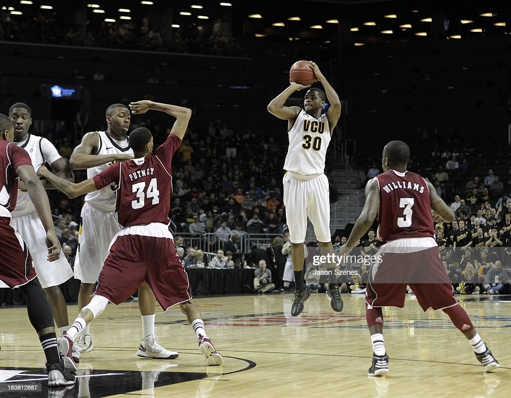 Troy Daniels #30 of the Virginia Commonweath Rams puts up a three point basket past Chaz WiIliams #3 of the Massachusetts Minutemen in the first half during the Atlantic 10 Basketball Tournament - Semifinals at the Barclays Center on March 16, 2013 in the Brooklyn borough of New York City.