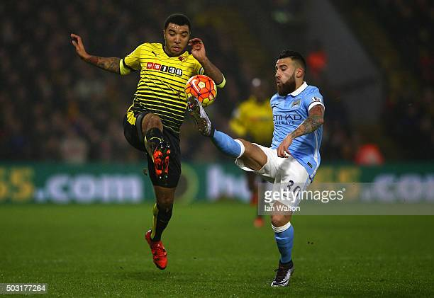 Troy Deeney of Watford battles for the ball with Nicolas Otamendi of Manchester City during the Barclays Premier League match between Watford and...