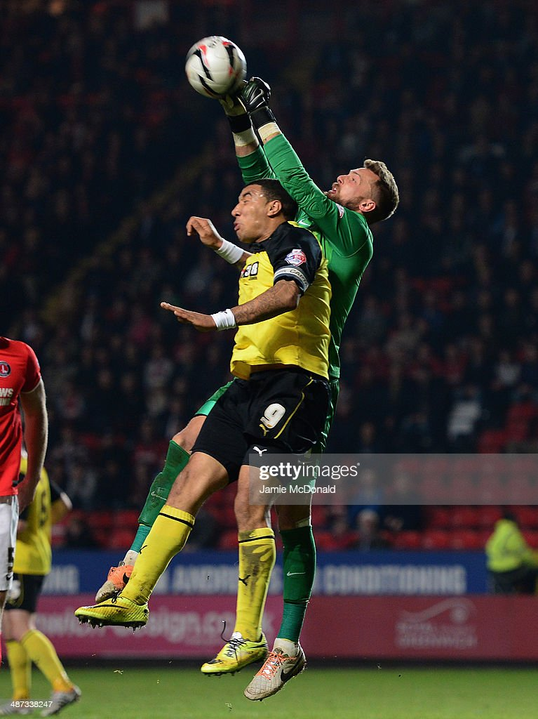 Troy Deeney of Watford cbattles with Ben Hamer of Charlton during the Sky Bet Championship match between Charlton Athletic and Watford at The Valley on April 29, 2014 in London, England.