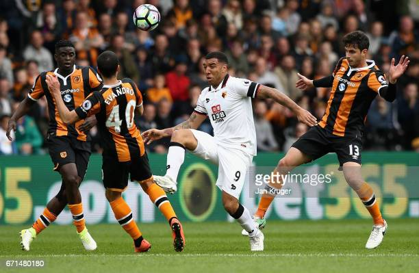 Troy Deeney of Watford challenges for the ball with Evandro and Andrea Ranocchia of Hull City during the Premier League match between Hull City and...