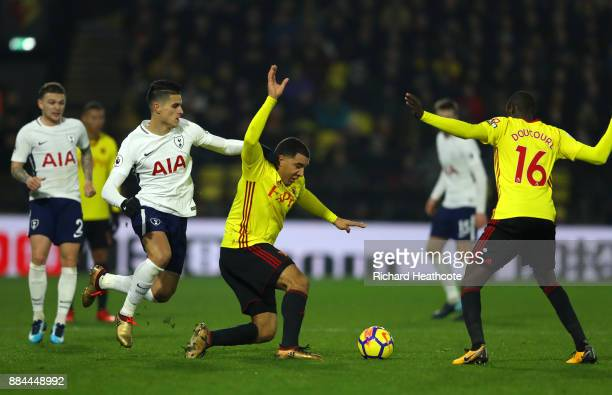 Troy Deeney of Watford is challenged by Erik Lamela of Tottenham Hotspur during the Premier League match between Watford and Tottenham Hotspur at...