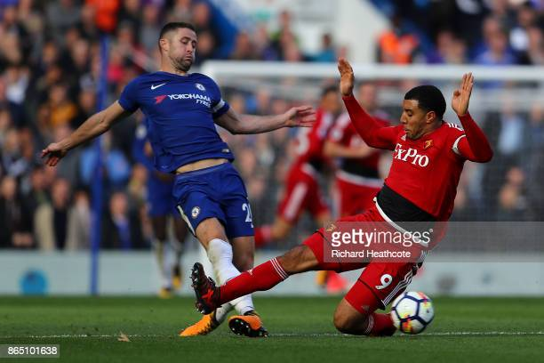 Troy Deeney of Watford tackles Gary Cahill of Chelsea during the Premier League match between Chelsea and Watford at Stamford Bridge on October 21...