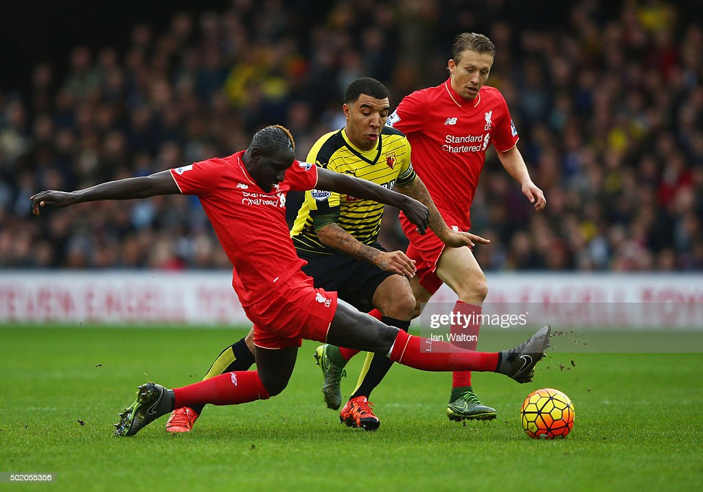 <a gi-track='captionPersonalityLinkClicked' href=/galleries/search?phrase=Troy+Deeney&family=editorial&specificpeople=4698410 ng-click='$event.stopPropagation()'>Troy Deeney</a> of Watford takes on <a gi-track='captionPersonalityLinkClicked' href=/galleries/search?phrase=Mamadou+Sakho&family=editorial&specificpeople=4154099 ng-click='$event.stopPropagation()'>Mamadou Sakho</a> and <a gi-track='captionPersonalityLinkClicked' href=/galleries/search?phrase=Lucas+Leiva+-+Defensive+Midfielder+-+Born+1987&family=editorial&specificpeople=4114250 ng-click='$event.stopPropagation()'>Lucas Leiva</a> of Liverpool during the Barclays Premier League match between Watford and Liverpool at Vicarage Road on December 20, 2015 in Watford, England.