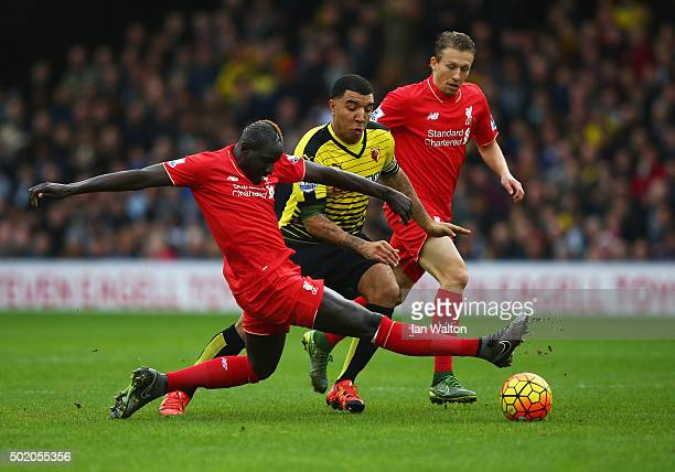 Troy Deeney of Watford takes on Mamadou Sakho and Lucas Leiva of Liverpool during the Barclays Premier League match between Watford and Liverpool at...