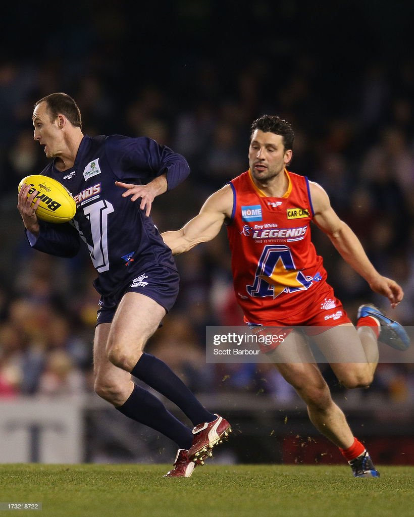 Troy Luff of Victoria runs with the ball during the EJ Whitten Legends AFL game between Victoria and the All Stars at Etihad Stadium on July 10, 2013 in Melbourne, Australia.