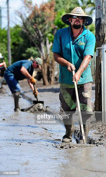 Troy Marshall helps clear out water and mud from the gutter in a street affected by flood waters on January 16 2011 in Rockhampton Australia...