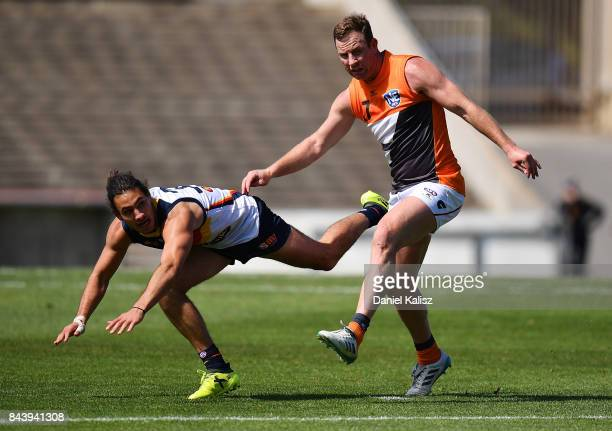 Troy Menzel of the Crows is bumped by Steve Johnson of the Giants during a practice match between the Greater Western Sydney Giants and the Adelaide...