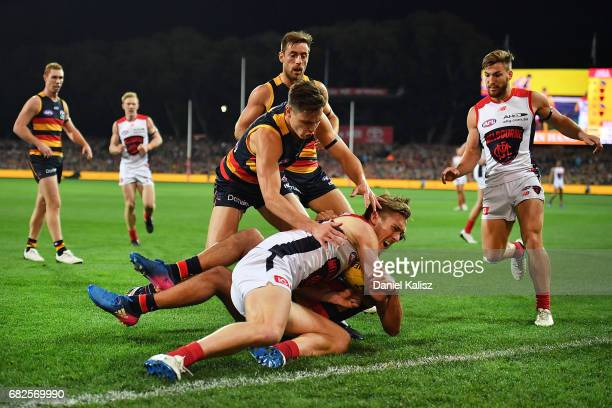 Troy Menzel of the Crows tackles Oscar McDonald of the Demons during the round eight AFL match between the Adelaide Crows and the Melbourne Demons at...