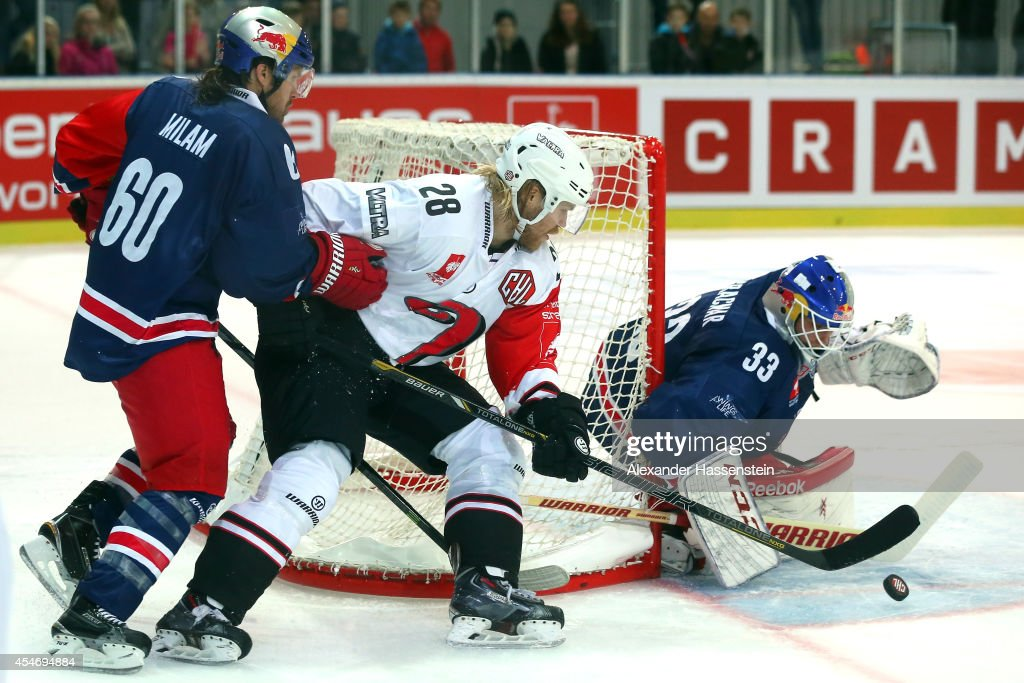 Troy Milam (L) of Salzburg and his goalie Luka Gracnar fights with Miika Lahti of Jyvaskyla during the Champions Hockey League group 1 between Red Bull Salzburg and JYP Jyvaskyla at Eisarena Salzburg on September 5, 2014 in Salzburg, Austria.