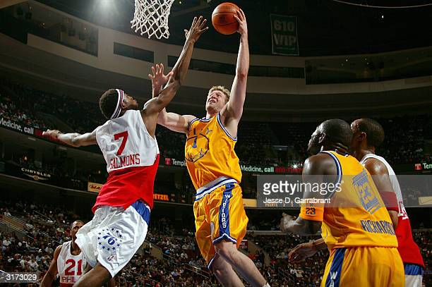Troy Murphy of the Golden State Warriors lays one up against John Salmons of the Philadelphia 76ers on March 30 2004 at the Wachovia Center in...