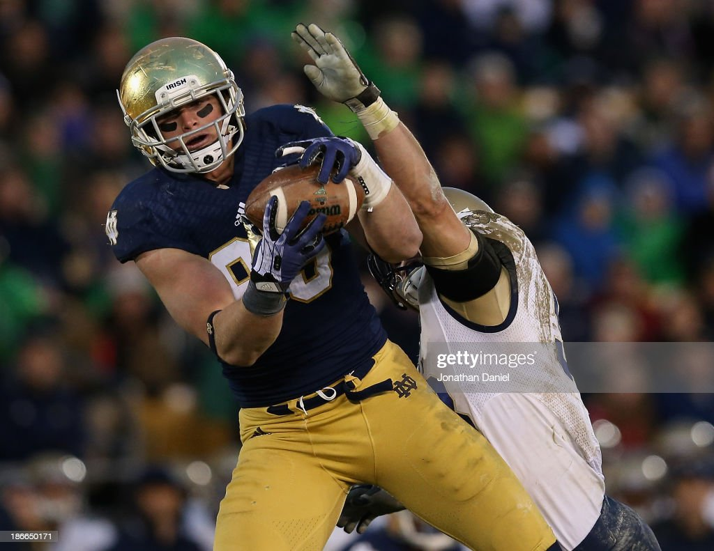 Troy Niklas of the Notre Dame Fighting Irish catches a first down pass in front of Cody Peterson of the Navy Midshipmen at Notre Dame Stadium on...
