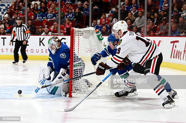 Troy Stecher of the Vancouver Canucks and Jonathan Toews of the Chicago Blackhawks reach for a rebound as Jacob Markstrom of the Vancouver Canucks...