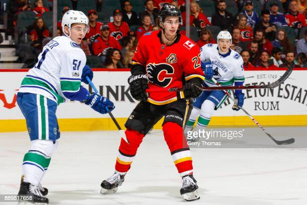 Troy Stecher of the Vancouver Canucks and Sean Monahan of the Calgary Flames in a NHL game against the Vancouver Canucks at the Scotiabank Saddledome...