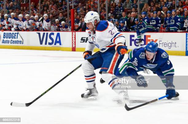 Troy Stecher of the Vancouver Canucks checks Milan Lucic of the Edmonton Oilers during their NHL game at Rogers Arena April 8 2017 in Vancouver...