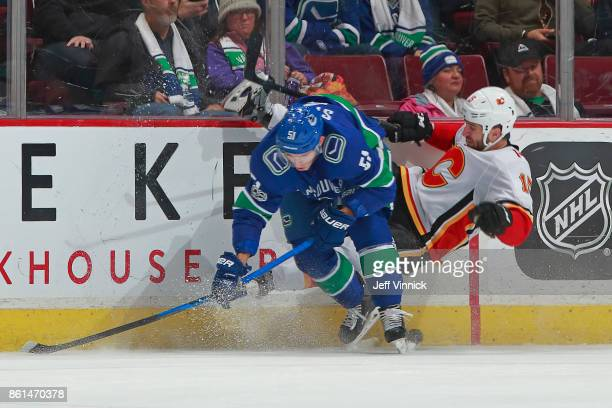 Troy Stecher of the Vancouver Canucks checks Tanner Glass of the Calgary Flames during their NHL game at Rogers Arena October 14 2017 in Vancouver...
